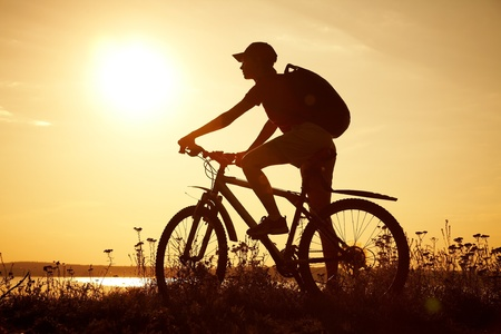 Silhouette of sports person cycling on the field on the beautiful sunset  Stock Photo - 10430535