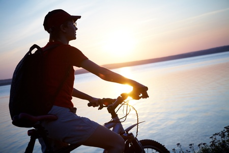 Silhouette of cyclist relaxing on the beautiful sunset Stock Photo - 10430529