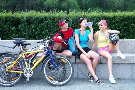Young pretty women resting after cycle race in the green park  photo