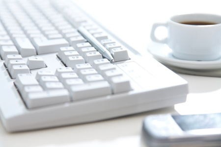 Clouse-up of white keyboard, cellphone, pen and a cup of coffee on the desktop Stock Photo - 10430543