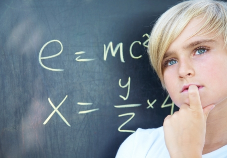 1 boy only: Schoolboy standing near blackboard with formula Stock Photo