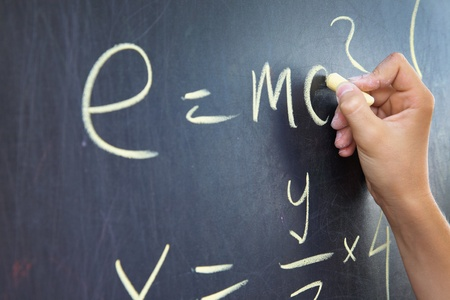 Close-up of student�s hand writing physics formula on blackboard Stock Photo - 10430570