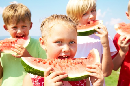 hungry kid: Children eating red watermelon on blue sky background Stock Photo