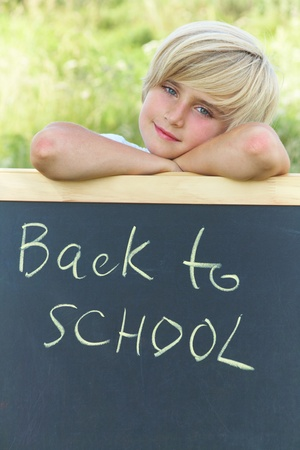 Cute schoolboy standing next to the blackboard with the text Stock Photo - 10430571