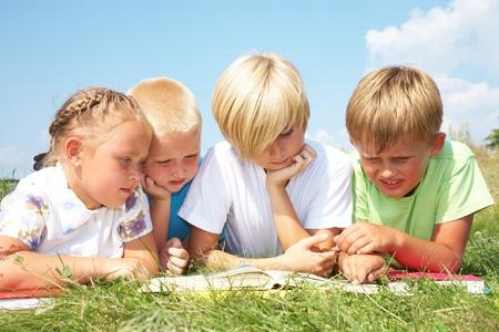 ni�os leyendo: ni�os en edad escolar primarias disfruta leyendo el mismo libro, bajo el sol por la tarde tarde