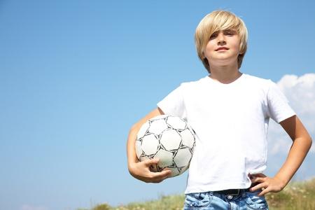 futbol infantil: Retrato de chicos adolescentes lindos con balón de fútbol contra el cielo azul