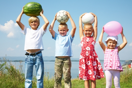 children playing together: Group of different children holding a watermelon, balls and balloon
