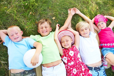 fall fun: Five cute children lying in green grass and enjoying summertime