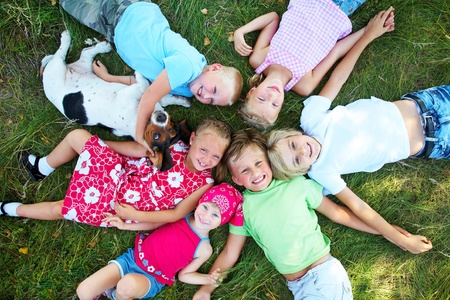 Six  cute children and dog lying in green grass and enjoying summertime photo