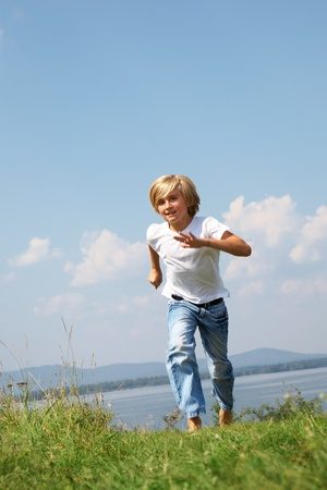 Young boy running on grass backgruond blue sky photo