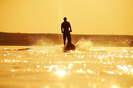 jet skier: strong man drives on the jetski above the water at sunset .silhouette spray.