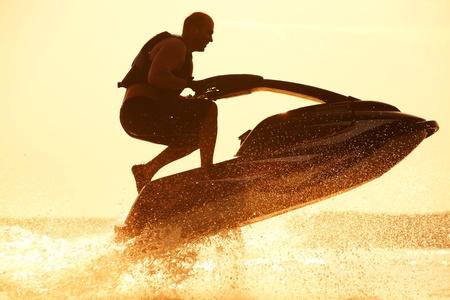 starken Mann springt auf den Jetski über das Wasser bei Sonnenuntergang. Silhouette Spray.