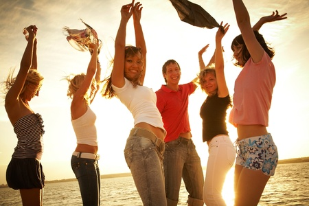 group of happy young people dancing at the beach on  beautiful summer sunset Stock Photo - 10430561