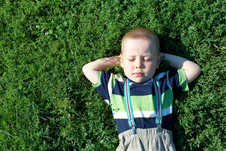 happy joyful  little boy sleeping on green lawn in summertime photo