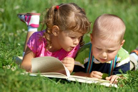 children enjoying reading the  book in green grass photo