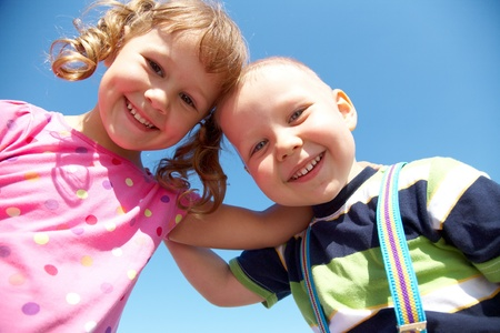 Portrait of a cheerful girl and boy blue sky background photo