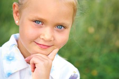 sweetly: Beautiful blue-eyed little girl smiling sweetly at the camera