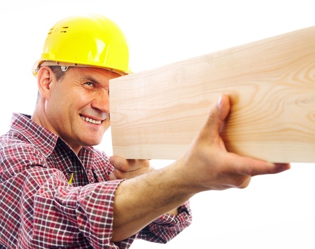 woodworker: handsome skilful carpenter measures the board isolated on white background