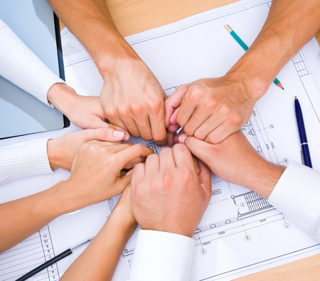 architect office: picture of hands to stay together over the table to show solidarity team