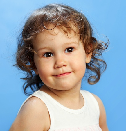Portrait of funny lovely little girl on the blue background Stock Photo - 10497200