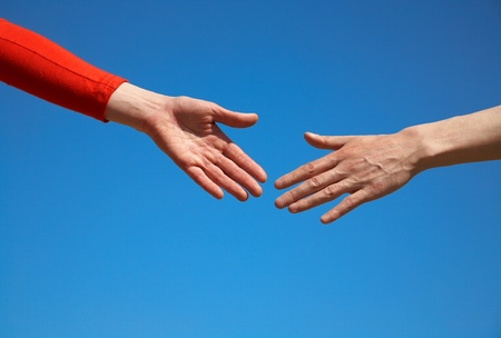 two arms stretching towards each other  to shake against the blue sky Stock Photo - 10491190