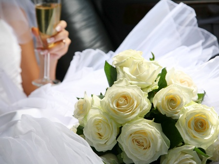 The bride with a wedding bouquet and champagne in a car photo