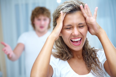 argument from love: Woman in foreground holding her head while angry man gestures behind her Stock Photo