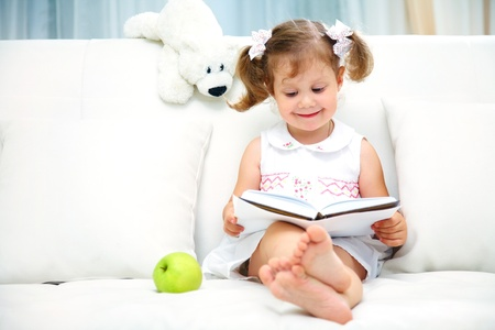 one story: Charming little girl reading book with her toy on white sofa