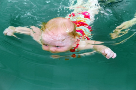 Underwater shot of cute baby in a swimming pool photo
