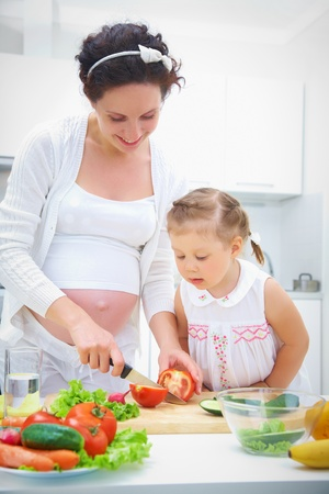 Pregnant mother and daughter in kitchen making a salad photo