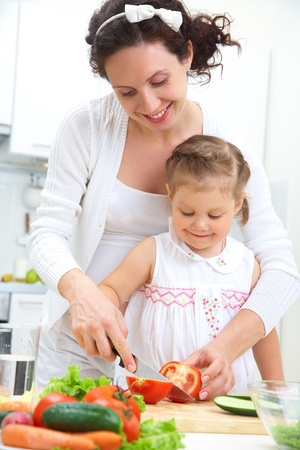 Mother and daughter in kitchen making a salad photo