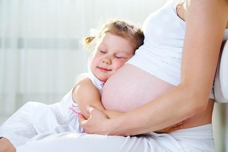 embarazada feliz: Linda ni�a abrazando a su madre embarazada