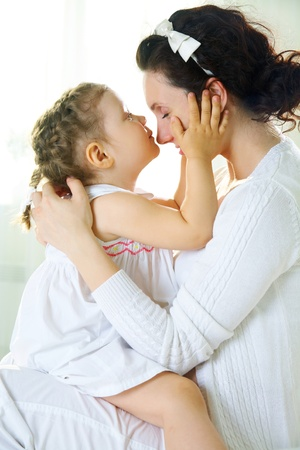 mother and child relationship: Little cute girl kissing her mother