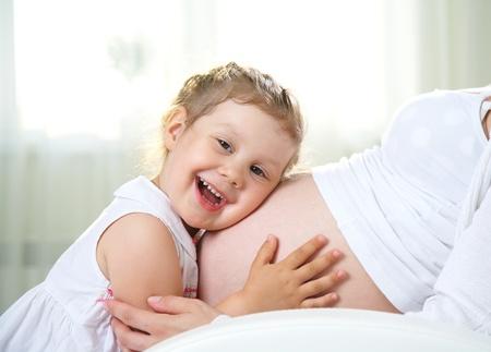 affetto: Piccola ragazza carina che abbraccia la madre incinta