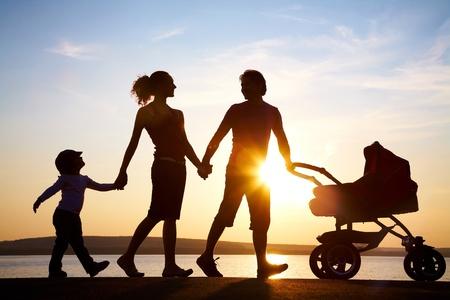 poussette: Silhouettes des parents heureux marche avec enfant et poussette sur le littoral