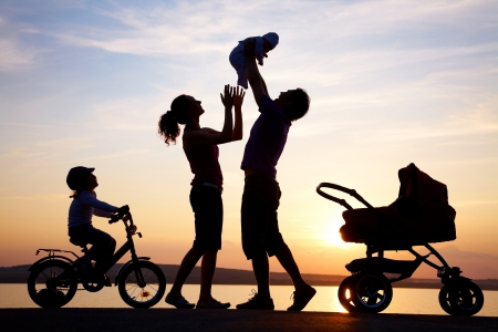 Silhouettes of happy parents having good time with their little children on the seacoast Stock Photo - 10511714