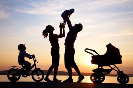 padres e hijos felices: Siluetas de padres felices tener buen tiempo con sus hijos pequeños en la costa