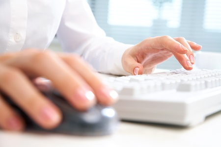 Detail of female hands using a computer on office background photo
