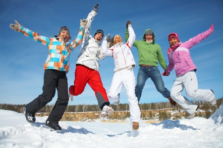 skiers: Group of  teenagers jumping together in wintertime Stock Photo