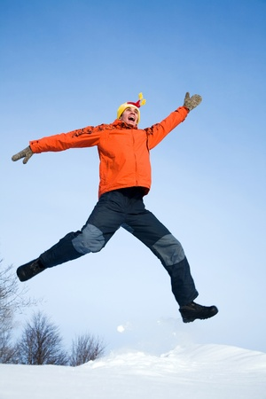 coldly: The young guy jumps with joy in the winter
