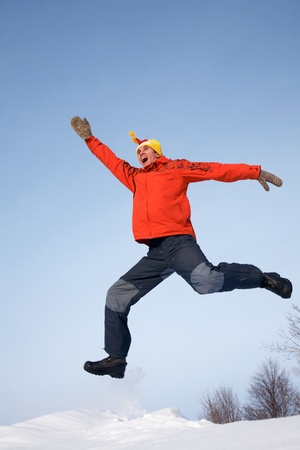 young guy jumps with joy in the winter photo