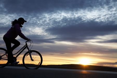 La bella ragazza è la bicicletta sul litorale su un tramonto