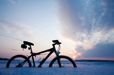 The lonely bicycle has got stuck in snow on the big lake