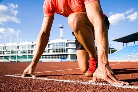 시작: 젊은 근육 운동 선수는 경기장에서 디딜 방아의 시작입니다 스톡 사진