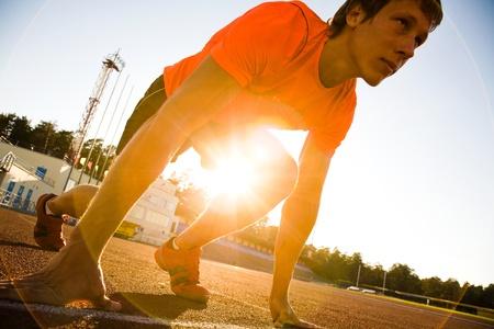 jungen muskul�sen Athleten am Start des Laufbandes im Stadion