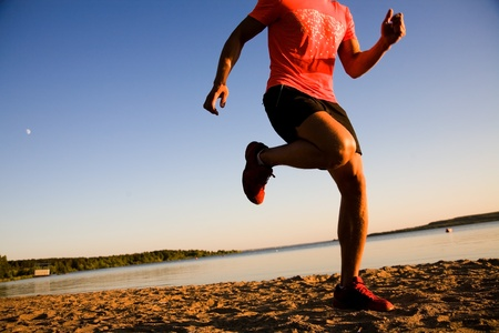 Young man running along the seashore at sunset. photo