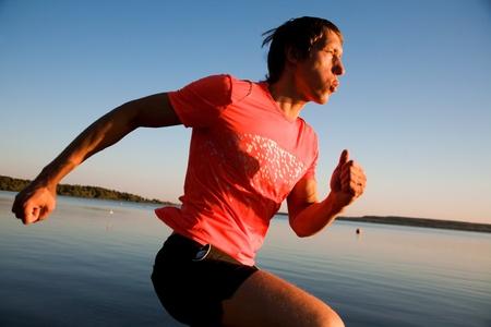 Young man running along the seashore at sunset Stock Photo - 10561846