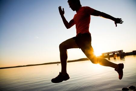 hombre deportista: Joven corriendo a lo largo de la orilla del mar al atardecer Foto de archivo
