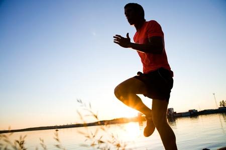 hombres corriendo: Joven corriendo a lo largo de la orilla del mar al atardecer Foto de archivo