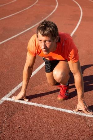 startpunt: jonge spier sporter aan het begin van de loopband het stadion